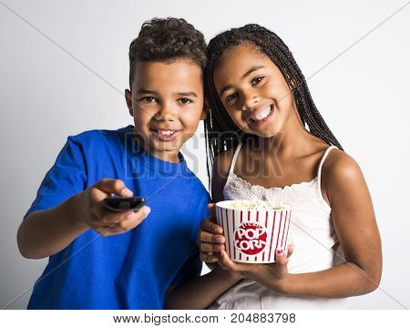 A black little boy and girl watching movie with pop corn