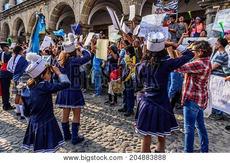 Antigua Guatemala - September 15 2017: School marching band stops & salutes locals protesting against government corruption in front of city hall on Guatemala's Independence Day.