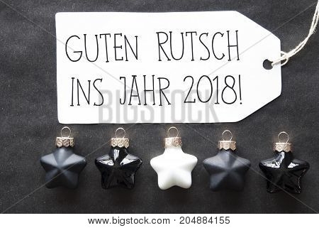 Label With German Text Guten Rutsch Ins Jahr 2018 Means Happy New Year 2018. Black And White Christmas Tree Balls On Black Paper Background. Christmas Decoration Or Texture. Flat Lay View