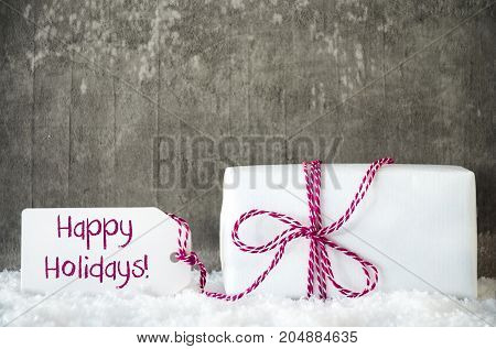 One White Gift With Label With English Text Happy Holidays. Gray Grungy Cement Background With Snow.