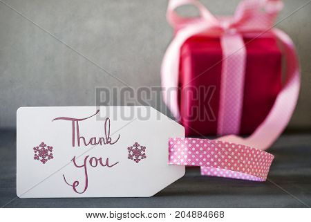 Label With English Calligraphy Thank You. Pink Present Or Gift With Gray Cement Background