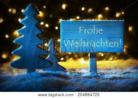 Sign With German Text Frohe Weihnachten Means Merry Christmas. Blue Christmas Tree With Snow And Magic Glowing Lights In Backround. Card For Seasons Greetings.