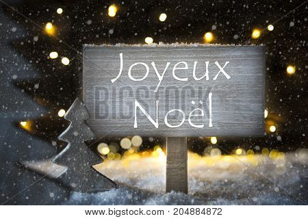 Sign With French Text Joyeux Noel Means Merry Christmas. White Christmas Tree With Snow And Magic Glowing Lights In Backround And Snowflakes. Card For Seasons Greetings.