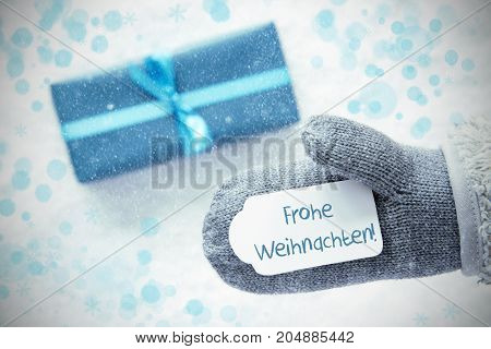 Glove With Label With German Text Frohe Weihnachten Means Merry Christmas. Turquoise Gift Or Present On Snow In Background. Seasonal Greeting Card With Snowflakes And Bokeh Effect