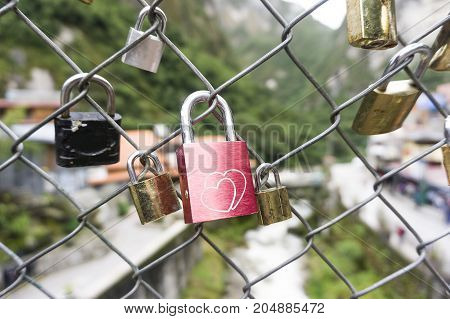A Red heart shaped lock padlock on the fence on the background
