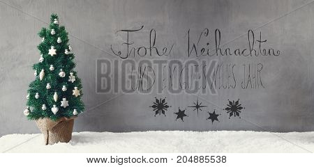 Calligraphy With German Text Frohe Weihnachten Und Ein Gutes Neues Jahr Means Merry Christmas And Happy New Year. Green Christmas Tree With Silver Christmas Ball Ornament On Snow.