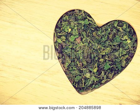 Dried Nettle Leaves Heart Shaped On Wooden Surface