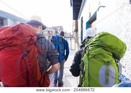 adventure, travel, tourism, hike and people concept - close up of friends walking with backpacks in Peru