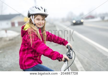 A Little girl riding a bike in a city
