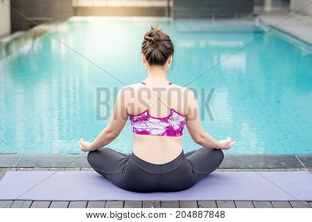 Beautiful young Asian woman doing yoga exercise with lotus position posing near swimming pool. Healthy lifestyle and good wellness concepts