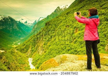 Tourism vacation and travel. Female tourist taking picture with camera enjoying scenic summer mountains landscape Norway Scandinavia.