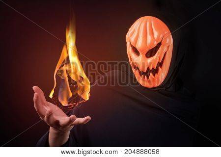 Mystery man with orange pumpkin evil mask control magic fireball on his hand Halloween night costume concept
