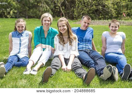 A Happy family members sitting in green grass outdoors