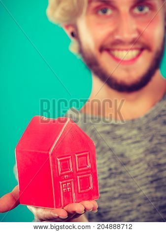 Household savings housekeeping concept. Smiling blonde man holding tiny red statue in shape of house. Studio shot on blue green background