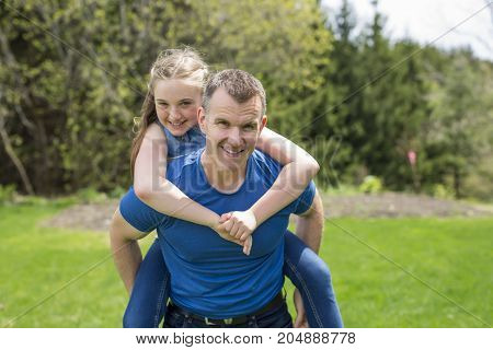 A portrait of a father carrying teen girl on back at the park