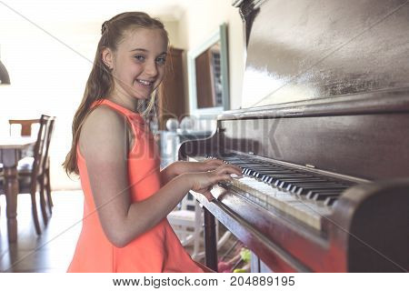 A girl Playing Piano at home having fun