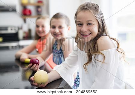 A Portrait of child girl with fruits in the kitchen