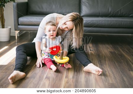 A Beautiful young mother playing and teaching her baby girl