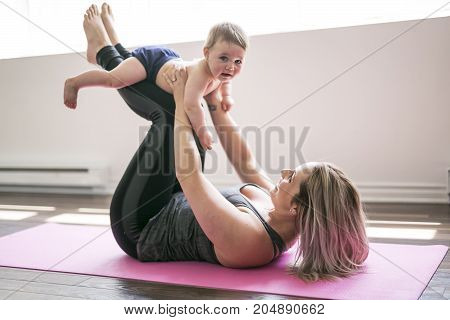 A young mother does physical yoga exercises together with her baby