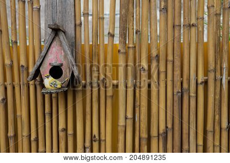Little bird house hanging on bamboo fence background.