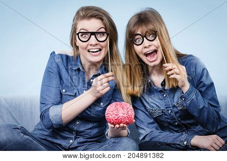 Friendship human relations concept. Two crazy women friends or sisters wearing jeans shirts and eyeglasses on stick thinking about solving problem holding fake brain