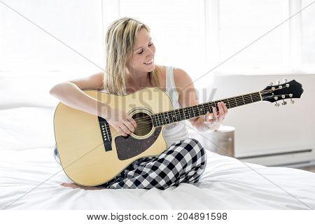 A Smiling woman with guitar sitting on the bed