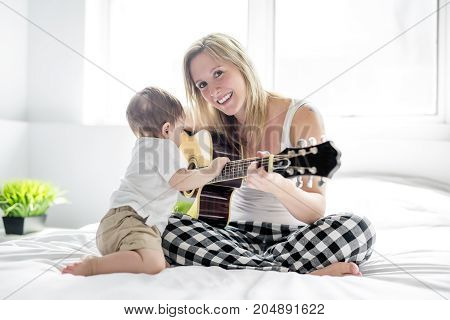A Smiling woman with guitar sitting on the bed with his child