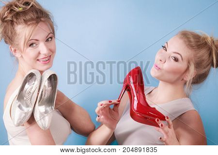 Attractive women fashion stylist presenting elegant shoes. Beautiful sensual high heels. Outfit accessories and footwear