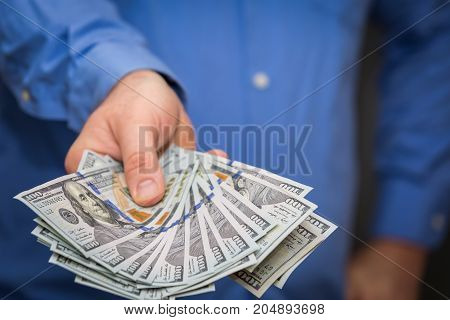 Holding out a fanned group of one hundred dollar bills