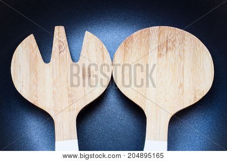 Close up of wooden spatula on coating pan background
