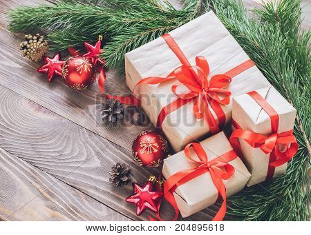 Christmas gifts in holiday boxes with red satin ribbons fir branches with cones Christmas toys balls on wooden background. New year's concept. The horizontal frame.Selective focus. Copy space