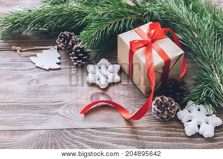 Christmas gifts in holiday boxes with red satin ribbons fir branches with cones Christmas decorations on wooden background. New year's concept. The horizontal frame.Selective focus. Copy space