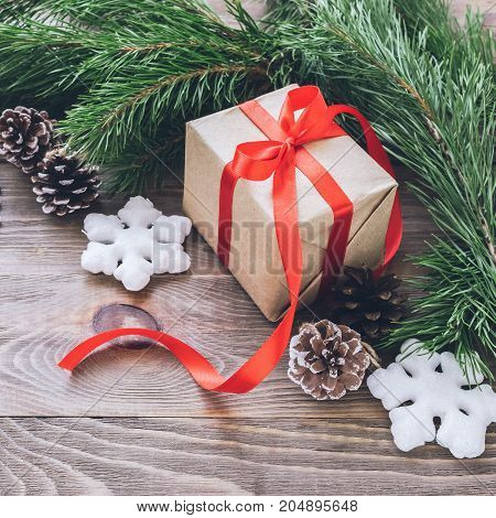 Christmas gift box with festive red satin ribbons fir branches with cones Christmas decorations on wooden background. New year's concept. A square frame.Selective focus.