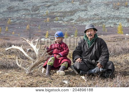 tsaatan nomadic boy and his grandfather in a traditional deels resting in a steppe in Northern Mongolia