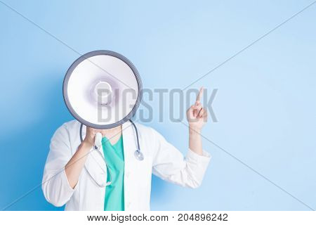 beauty woman dentist take microphone and show somethimg on the blue background