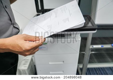 close up businessman hold documents for scanning on the office printer