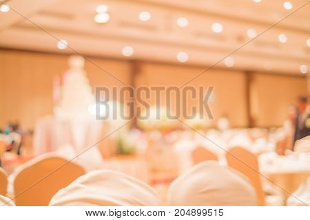 Abstract blurred image of Large dining table set for wedding dinner or festival event with beautiful lights decoration inside large hall. ceremony.