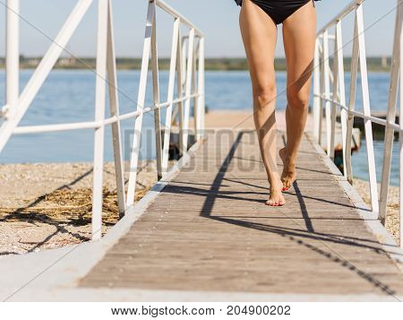 Close-up stunning slim female's legs walking on pier on a natural background. Girl in swimsuit near the river. Copy space.