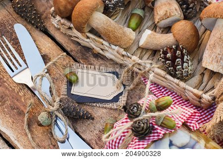 Vegetarian set: raw white mushrooms pine cones with different decorations and decorative tag on the wooden table