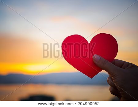 Hand holding the red paper heart with blur sunlight during sunset Valentines day.