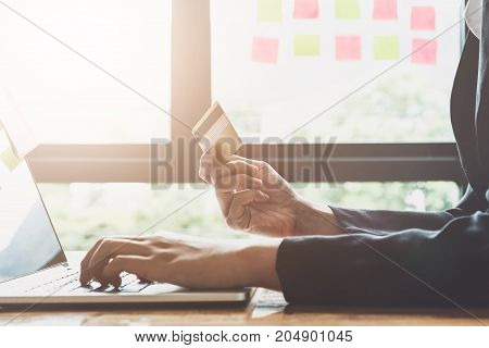 Young Woman Holding Credit Card And Using Laptop Computer. Online Shopping Concept With Vintage Filt
