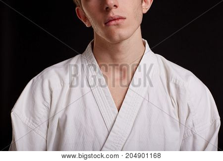 Close-up picture of a confident judo fighter in a traditional kimono on the black background. Sports lifestyle concept.