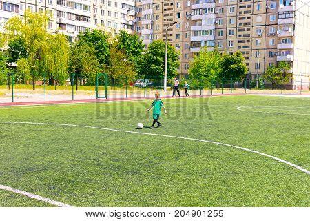 Kyiv, Ukraine - May 21, 2017: The small boy training at Soccer Football field at the schoolyard at Kiev, Ukraine