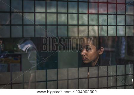Old Delhi India : February 15th 2015 - A shot of an indian girl looking out the window off a shop in Old Delhi India.