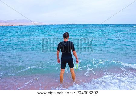 Young Man In Diving Suit Goes To Sea In abstract Summer Outdoors