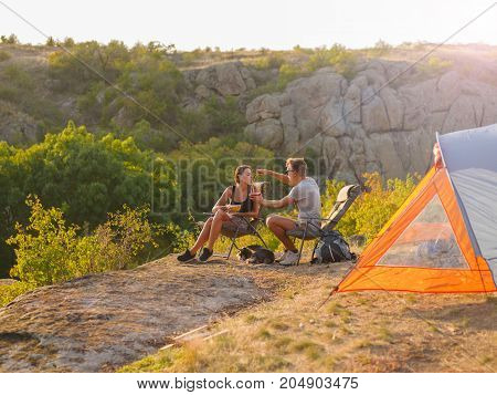 Girlfriend and boyfriend eating and relaxing near tent on a natural background. Young girl and man enjoying a beautiful view of mountains and forest. Travelling, camping, hiking, concept. Copy space.