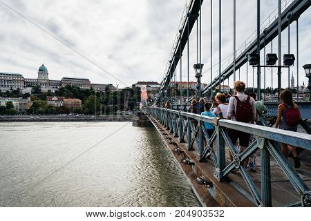 Budapest, Hungary - August 12, 2017: People crossing the Chain Bridge. It is a suspension bridge that spans the River Danube between Buda and Pest, was the first permanent bridge across the Danube .