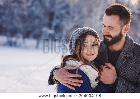 happy loving couple walking in snowy winter forest spending christmas vacation together. Outdoor seasonal activities. Lifestyle capture.