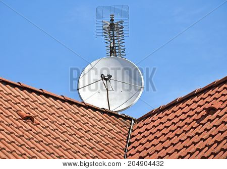 Satellite dish and television antenna on the roof of a building