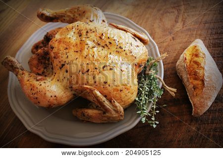 Whole roasted chicken with thyme and bread on wooden background .